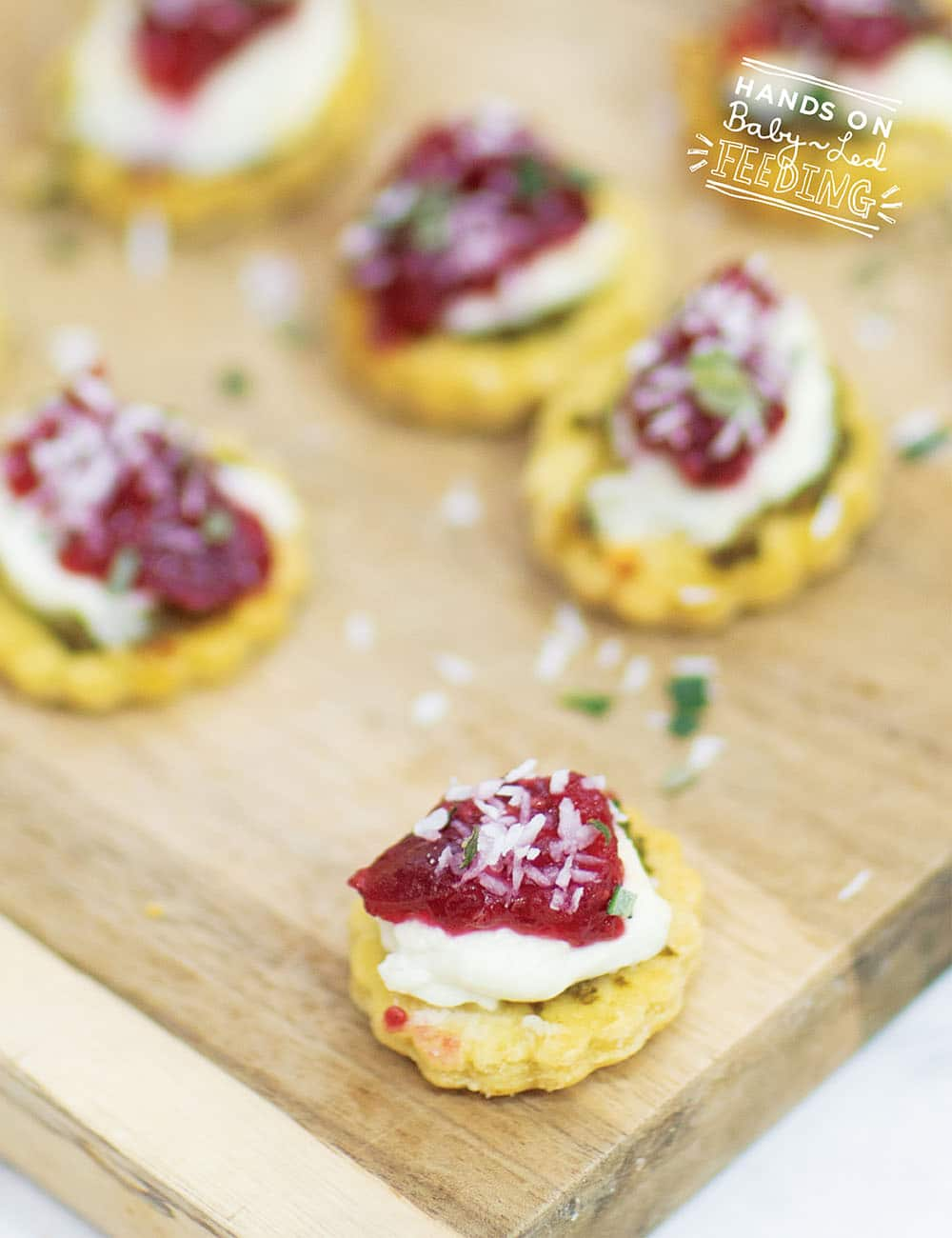 Healthy Christmas Appetizers are not always easy to find... But here is a fresh and super easy appetizer that is safe for babies and toddlers too! Goat cheese, cranberries, pesto and coconut all on top of a fresh baked crust. Merry Christmas! #appetizer #christmasrecipe #babyledweaning